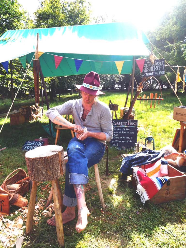 Family festival bushcraft: demonstrations on how to make a wooden spoon, butter knife, musical instruments, ores and more. Into The Trees festival, Sussex, September 2017.