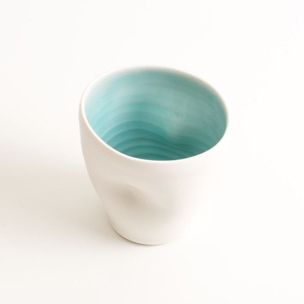 Handmade Dimpled Cup turquoise Glaze. With a matt white glaze on the outside and soft coloured inside. Available in pale blue, pale pink, grey and turquoise. Perfectly formed dimples to fit in your hand, where the shape is inspired by Japanese tea traditions. Handmade by Linda Bloomfield in London. Sold on chalkandmoss.com.