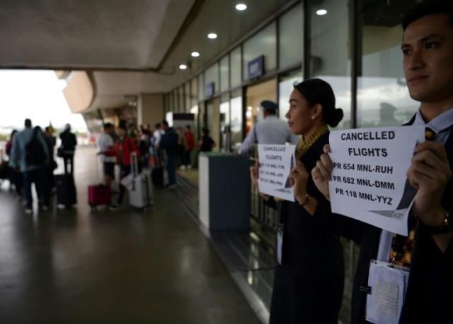 Du personnel de compagnies aériennes annoncent l'annulation de vols à l'aéroport international de Manille fermé en raison du typhon Kammuri, le 3 décembre 2019 (AFP - Ted ALJIBE)