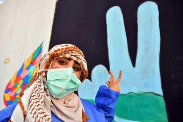 Une manifestante irakienne fait le signe de la victoire devant un graffiti antigouvernemental, à Najaf, dans le centre de l'Irak, le 18 décembre 2019 (AFP - Haidar HAMDANI)