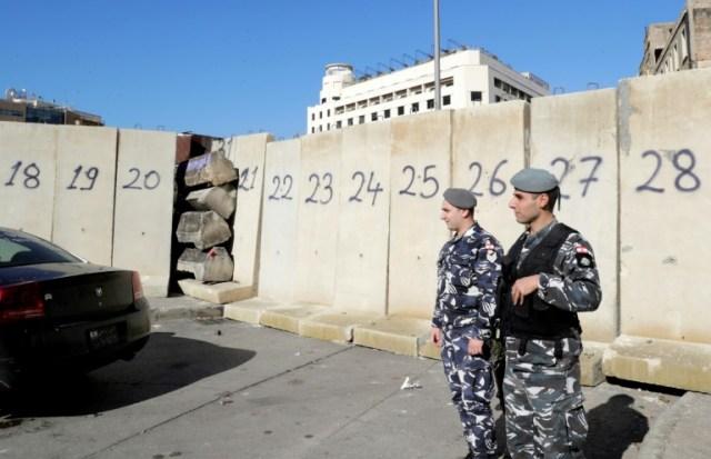 Des policiers libanais devant des barricades installées pour bloquer les routes menant aux places de la contestation dans le centre-ville de Beyrouth le 18 décembre 2019  (AFP - ANWAR AMRO)