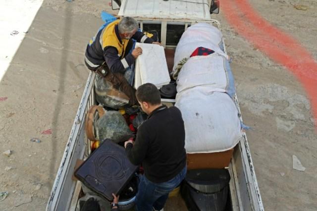 Des secouristes aident des Syriens à fui les bombardements sur la ville de Maaret al-Noome dans le nord-ouest de la Syrie, le 20 décembre 2019 (AFP - Omar HAJ KADOUR)