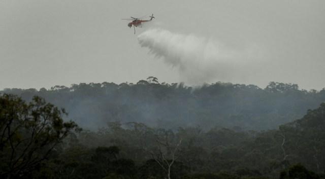 Un hélicoptère bombardier d'eau déverse son chargement sur un incendie, le 30 décembre 2019 dans une banlieue de Melbourne (AFP - William WEST)