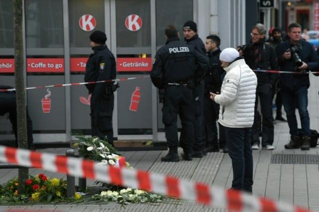 Un homm s'incline devant un hommage improvisé aux victimes de la tuerie de Hanau, le 20 février 2020 (AFP - Patrick HERTZOG)