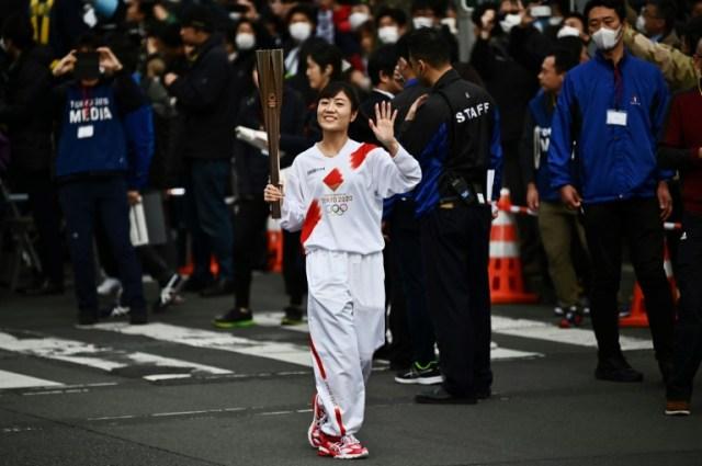 Le relais de la flamme olympique devant une poignée de gens à Tokyo, le 15 février 2020 (AFP/Archives - CHARLY TRIBALLEAU)