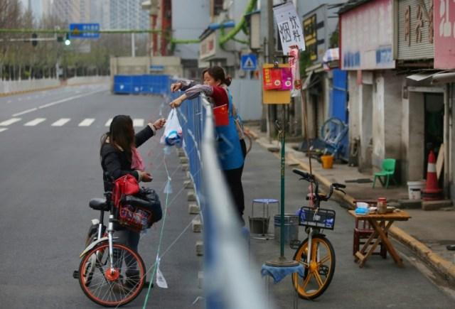Livraison de nourriture par-dessus une barrière, le 16 mars 2020 à Wuhan, pendant l'épidémie du nouveau coronavirus (AFP - STR)