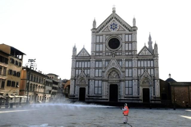 Désinfection du parvis de la basilique Santa Croce, le 21 mars 2020 à Florence  (AFP - Carlo BRESSAN)