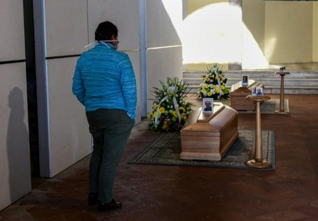 Une femme devant le cercueil d'un proche dans le cimetière de Zogno, près de Bergamo, (nord de l'Italie), le 21 mars 2020  (AFP - Piero Cruciatti)