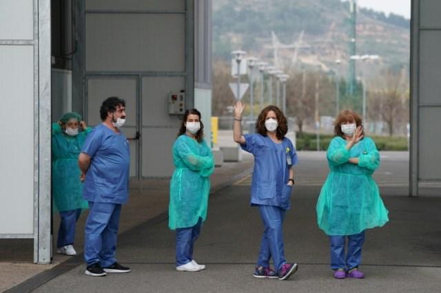 Des membres du personnel soignant prennent quelques minutes de pause devant l'hôpital de Burgos, dans le nord de l'Espagne, le 20 mars 2020 (AFP/Archives - CESAR MANSO)