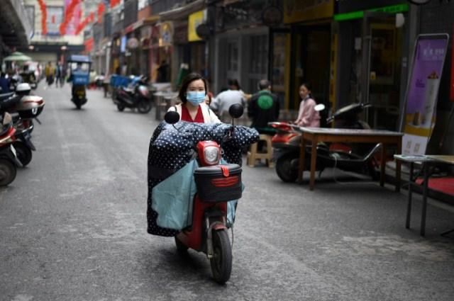 Une femme à moto, le visage couvert d'un masque de protection, dans une rue de Huanggang, dans la province chinoise du Hubei, le 26 mars 2020 (AFP - Noel Celis)