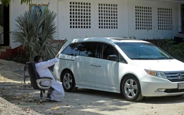 Un prêtre catholique entend la confession d'un fidèle en voiture, à Acapulco (Mexique) le 9 avril 2020 (AFP - Francisco Robles)