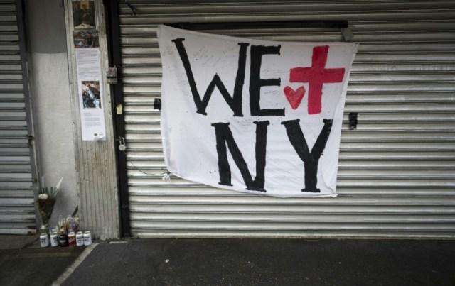 Un magasin fermé dans le quartier de Queens, à New York, près d'un mini-mémorial à une victime du coronavirus, le 14 avril 2020 (AFP - Johannes EISELE)