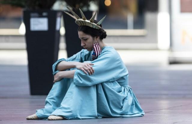 Une femme déguisée en statue de la liberté est assise à Times Square, New York, le 15 mai 2020  (AFP - Johannes EISELE)