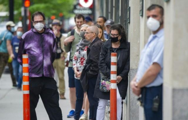 De nombreux clients patientent à l'extérieur du magasin Simons pour la réouverture, à Montréal (Canada), le 25 mai 2020  (AFP - Sebastien St-Jean)