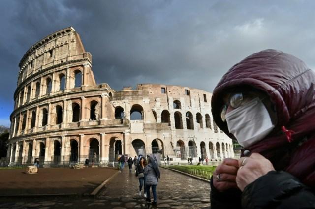 Un homme portant un masque de protection passe devant le Colisée à Rome le 7 mars 2020  (AFP - Alberto PIZZOLI)