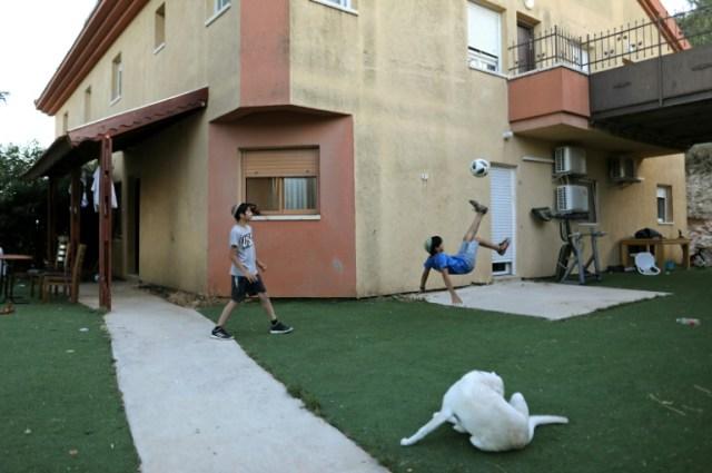 Des enfants de colons israéliens jouent près de leur maison, à Otniel, une colonie juive, en Cisjordanie occupée, le 3 juin 2020 (AFP - MENAHEM KAHANA)