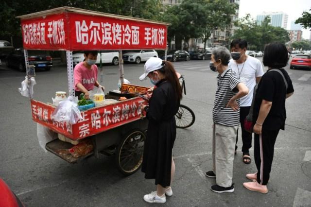 Des gens font la queue pour acheter de la nourriture à un vendeur de rue installé sur un carrefour à Pékin, le 9 juin 2020 (AFP - GREG BAKER)