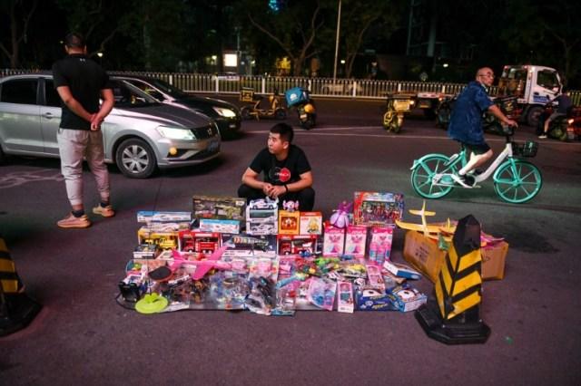 Un homme vend des jouets au bord d'une route devant un centre commercial à Pékin, le 10 juin 2020 (AFP - GREG BAKER)