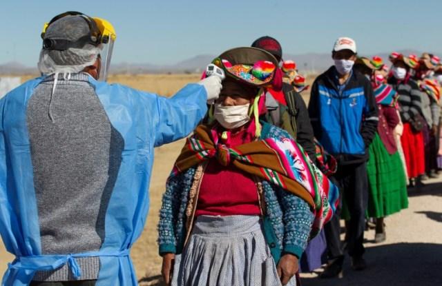 Prises de température d' habitants se rendant au marché de Coata, à 40 km de Puno, au Pérou, une ville proche de la frontière avec la Bolivie, le 8 juillet 2020  (AFP/Archives - Carlos MAMANI)