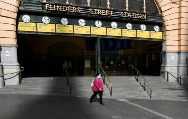 Une femme passe devant l'entrée de la gare de Flinders Street déserte, le 3 août 2020 à Melbourne, en Australie (AFP - William WEST)