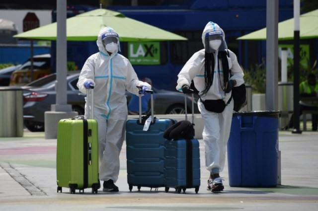 Des voyageurs en combinaison intégrale de protection à l'aéroort de Los Angeles, le 20 août 2020 en Californie (AFP - Robyn Beck)