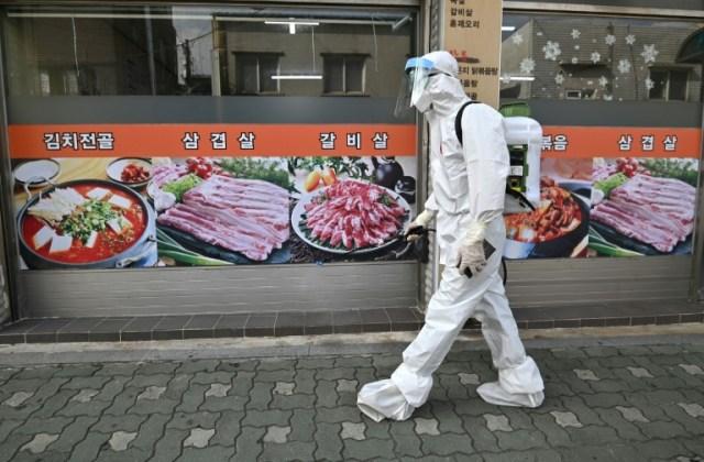 Un employé sud-coréen vêtu d'une combinaison de protection contre le coronavirus désinfecte une rue à Séoul le 18 août 2020. (AFP - Jung Yeon-je)
