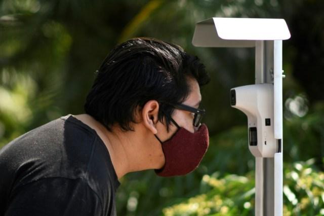 Un homme vérifie sa température avant d'entrer dans un zoo au Guatemala le 25 août 2020 (AFP - Johan ORDONEZ)