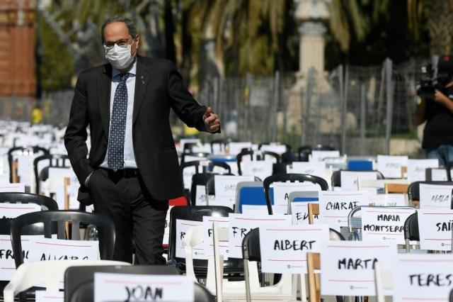 Le président régional catalan Quim Torra visite une installation de chaises représentant chacune un militant séparatiste poursuivi par la justice espagnole, le 11 septembre 2020 à Barcelone (AFP - Josep LAGO)