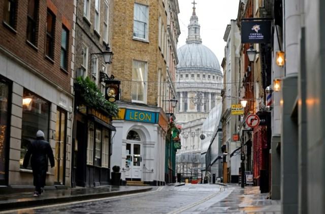 Une personne marche dans une rue de Londres rendue déserte par le confinement, le 5 janvier 2021 (AFP - Tolga Akmen)