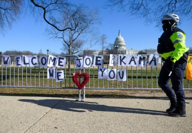 un policier passe devant une banderole souhaitant la bienvenue à la future vice-président Kamala Harris près du Capitole le 10 janvier 2021 (AFP - Andrew CABALLERO-REYNOLDS)
