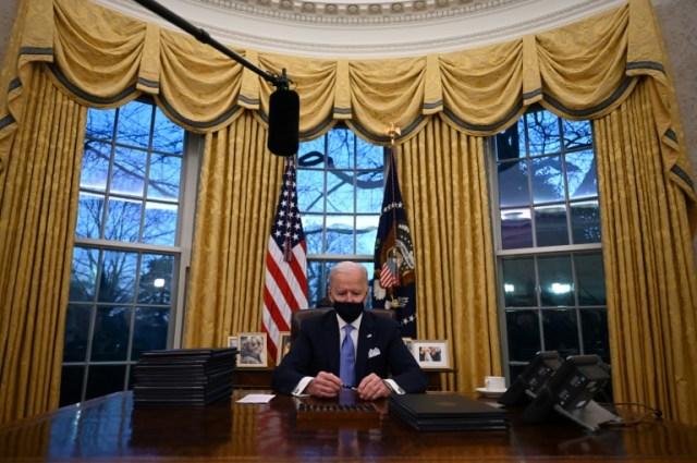 Le président américain Joe Biden signe une série de décrets, dont l'arrêt de la construction du mur à la frontière mexicaine, le 20 janvier 2021, à Washington  (AFP - Jim WATSON)