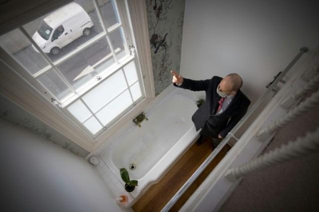 L'agent immobilier David Myers fait visiter la plus étroite maison de Londres (Royaume-Uni), le 5 février 2021 (AFP - Tolga Akmen)
