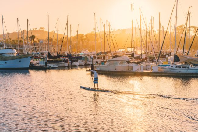 man paddle boarding past yacht