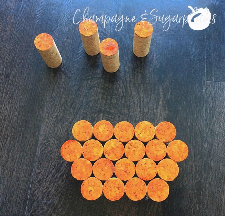 Rows of corks being glued together into a pumpkin shape by Champagne and Sugarplums