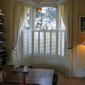 Simple lined linen curtains on bay window track with cafe shutters for