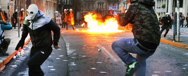Protesters run away from police after hurling petrol bombs during violent anti-austerity demonstration in central Athens (Reuters)