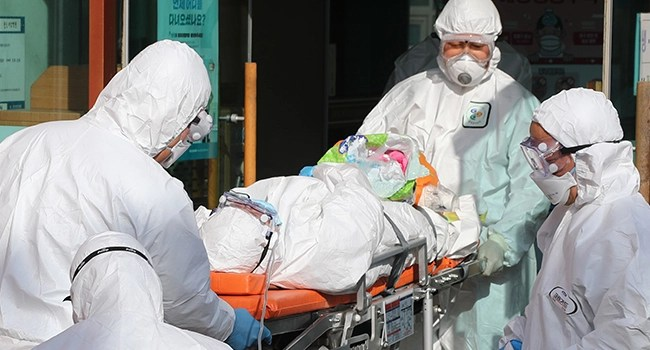 Medical workers wearing protective gear transfer a suspected coronavirus patient (C) to another hospital from Daenam Hospital where a total of 16 infections have now been identified with the COVID-19 coronavirus, in Cheongdo county near the southeastern city of Daegu on February 21, 2020. YONHAP / AFP