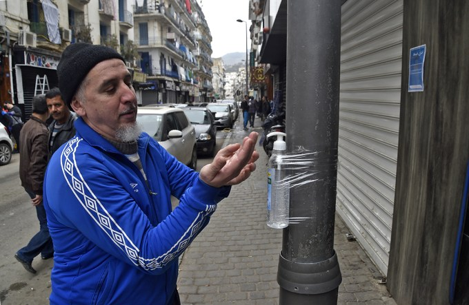 An Algerian man disinfects his hands with alcohol gel attached to a pole in Algiers' Bab el-Oued district on March 20, 2020. - A total of 82 cases of coronavirus COVID-19 have been confirmed in Algeria, according to the health ministry. An 83rd case was detected in an Italian national, who has since returned to Italy. Two more virus deaths were registered in Algeria yesterday, the health ministry said, bringing to eight the number of fatalities from COVID-19 since the first case was registered in the country at the end of February. Photo: AFP