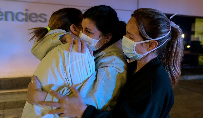 Healthcare workers dealing with the new coronavirus crisis in Spain, hug each other as they are cheered on by people outside La Fe hospital in Valencia on March 26, 2020. - Spain's coronavirus toll surged above 4,000 today but the increase in both fatalities and infections slowed, raising hope a nationwide lockdown was starting to curb the spread of the epidemic. Spain currently has the world's second highest death toll after Italy, and has so far suffered 4,089 deaths after another 655 people succumbed to the virus in the past 24 hours, the health ministry said. (Photo by JOSE JORDAN / AFP)