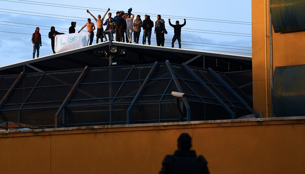 A police officer watches a group of illegal immigrants protesting on the roof of the Aluche Immigration Detention Center