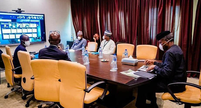 Vice President Yemi Osinbajo (right) wears a mask during a meeting. Photo: Tolani Alli