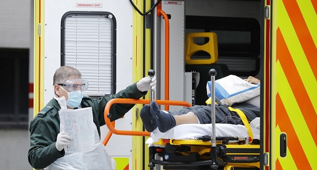 File: A member of the ambulance services assists in moving a patient from an ambulance to St Thomas' Hospital in London on March 31, 2020, as the country is under lockdown due to the novel coronavirus COVID-19 pandemic. Tolga AKMEN / AFP.
