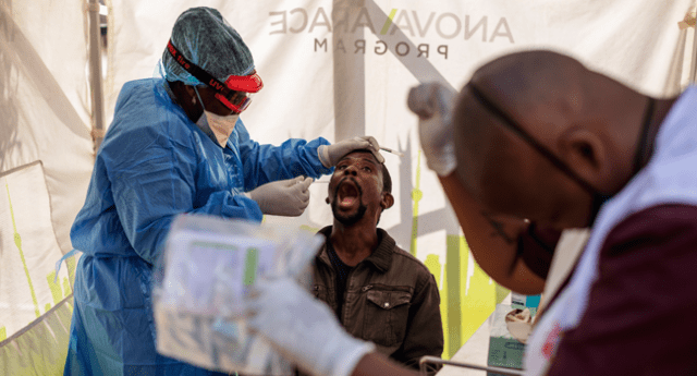 Doctors Without Borders (MSF) nurse Bhelekazi Mdlalose (L), 51, performs a swab test for COVID-19 coronavirus on a health worker at the Vlakfontein Clinic in Lenasia, Johannesburg, on May 13, 2020. Michele Spatari / AFP
