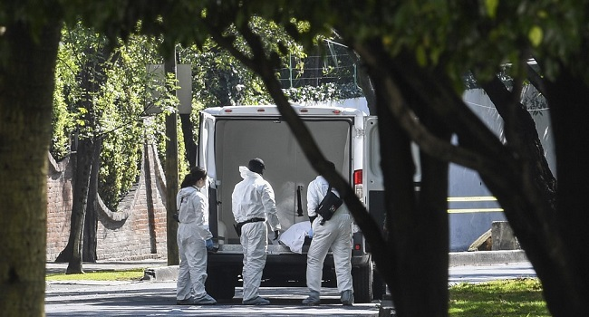 Forensic experts remove a corpse from the crime scene after Mexico City's Public Security Secretary Omar Garcia Harfuch attacked in Mexico City, on June 26, 2020. - Mexico City's security chief was wounded in a gun attack Friday in which two of his bodyguards and a woman passerby were killed, Mayor Claudia Sheinbaum said. (Photo by PEDRO PARDO / AFP)