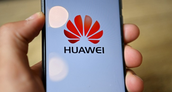 The logo of Chinese company Huawei is seen on the screen of a Huawei mobile phone held in the photographer's hand in London on July 14, 2020. - Britain on Tuesday ordered its telecom providers to stop purchasing 5G equipment from China's Huawei giant from the start of next year, and to strip out all of its equipment by 2027. (Photo by DANIEL LEAL-OLIVAS / AFP)