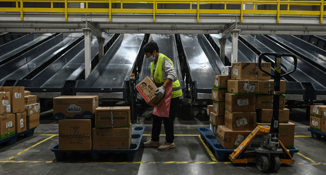 In this picture taken on November 6, 2020, an employee works in the warehouse of Cainiao Smart Logistics Network, the logistics affiliate of e-commerce giant Alibaba, in Wuxi, China's eastern Jiangsu province, ahead of Singles' Day, also known as the Double 11 shopping festival - the world's biggest shopping event - which falls on November 11. Hector RETAMAL / AFP