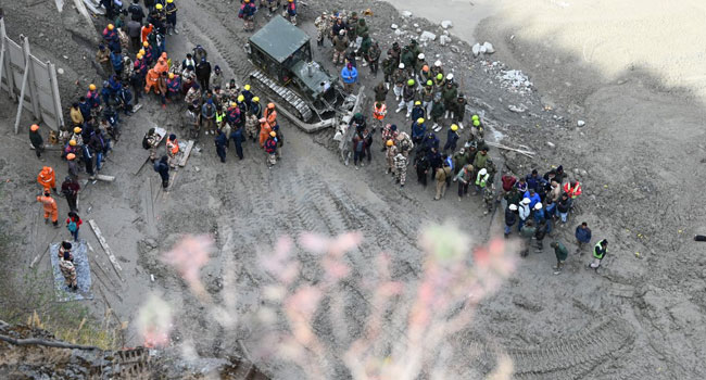 Rescue teams gather near the entrance of a tunnel blocked with mud and debris, where workers are trapped, in Tapovan of Chamoli district on February 9, 2021 following a flash flood thought to have been caused when a glacier burst on February 7. Sajjad HUSSAIN / AFP