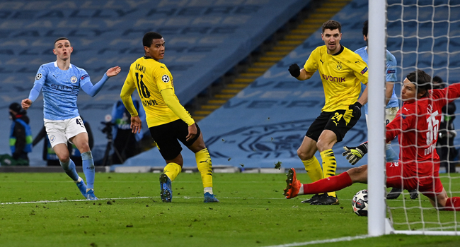 Manchester City's English midfielder Phil Foden (L) scores his team's second goal during the UEFA Champions League first leg quarter-final football match between Manchester City and Borussia Dortmund at the Etihad Stadium in Manchester, north west England, on April 6, 2021. Paul ELLIS / AFP