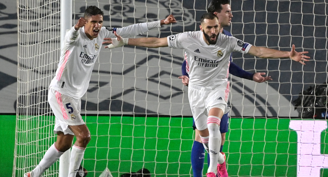 Real Madrid's French forward Karim Benzema (R) celebrates after scoring during the UEFA Champions League semi-final first leg football match between Real Madrid and Chelsea at the Alfredo di Stefano stadium in Valdebebas, on the outskirts of Madrid, on April 27, 2021. JAVIER SORIANO / AFP