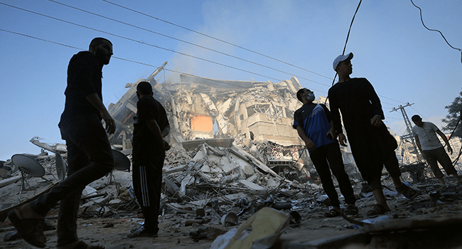Palestinian men stand amidst debris near the al-Sharouk tower, which housed the bureau of the Al-Aqsa television channel in the Hamas-controlled Gaza Strip, after it was destroyed by an Israeli air strike, in Gaza City, on May 13, 2021.  MOHAMMED ABED / AFP